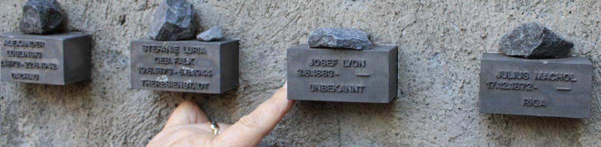 """Gisela Jäckel vor der Mauer am Museum """"Jüdisches Ghetto"""" in Frankfurt und zeit auf die Tafel von Jpseph Lyon"""